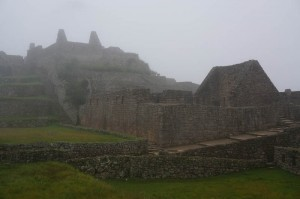 A very foggy Machu Picchu. To the right is part of a town and the higher part of the building was a temple