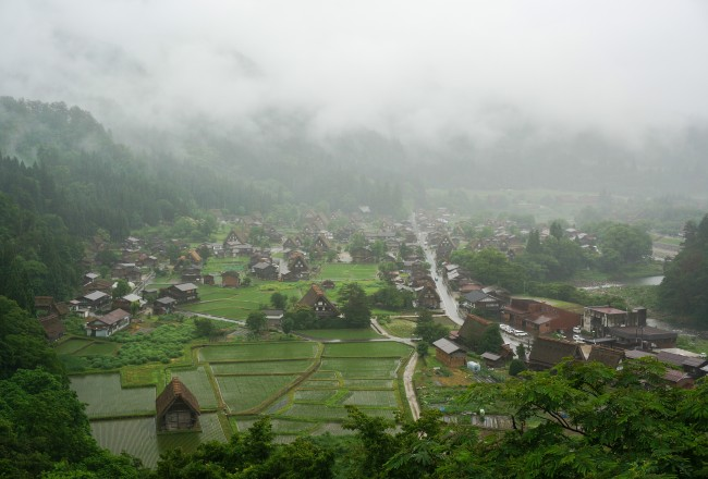 Shrouded in clouds - the traditional handwoven thatch roofed houses of Shirakawa-go stand silently in the rain